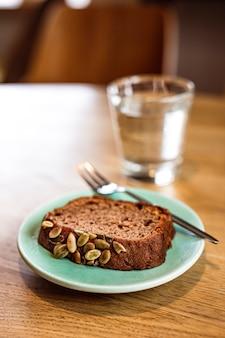 Кусочек бананового хлеба с тыквенными семечками на синей тарелке, десертная вилка, стакан воды. деревянный стол, кафе.