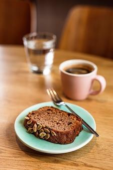 Кусочек бананового хлеба с тыквенными семечками на синей тарелке, десертная вилка, розовая чашка горячего черного кофе, стакан воды. деревянный стол, кафе.
