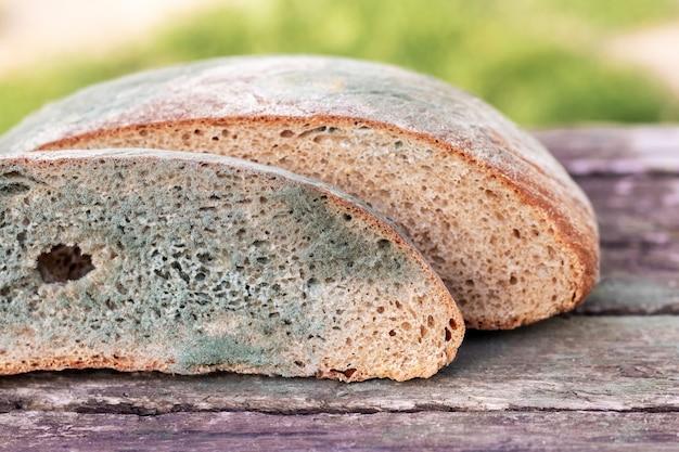 Ломтик хлеба, покрытый плесенью, на деревянной поверхности