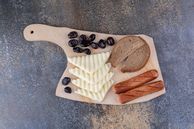 Кусочек хлеба с сосисками и сыром на деревянной доске