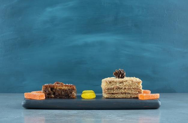 Кусочек торта, пахлава и несколько желейных конфет на темно-синем фоне на мраморной поверхности