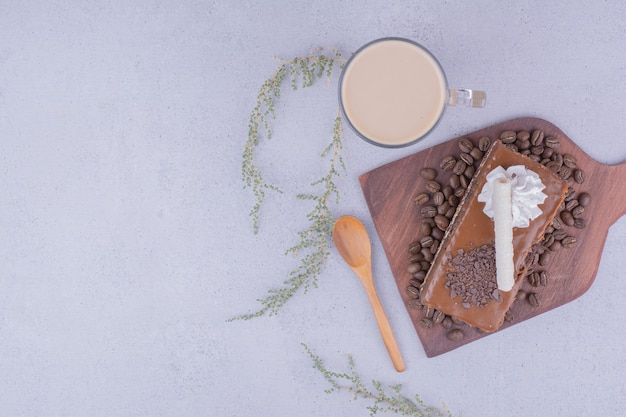 라떼 한잔과 함께 나무 접시에 카라멜 케이크 한 조각