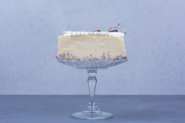 青い背景のガラス受け皿にチーズケーキのスライス