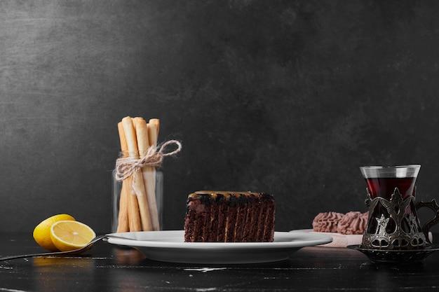 차 한 잔 함께 하얀 접시에 초콜릿 케이크 한 조각.