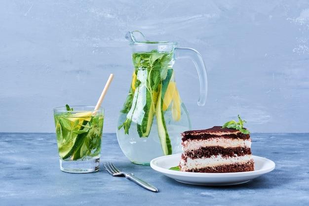 Кусочек шоколадного торта в белой тарелке с коктейлем мохито.