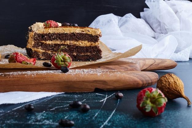 Кусочек шоколадного торта на деревянной доске.