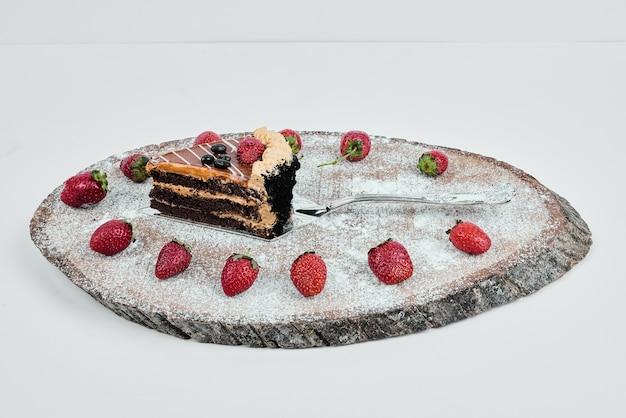 나무 보드에 초콜릿 케이크 한 조각.