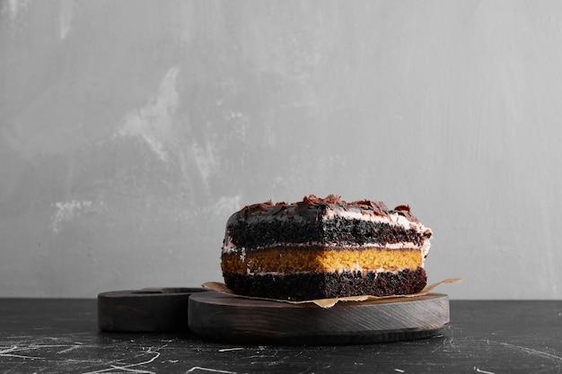 나무 접시에 초콜릿 케이크 한 조각.