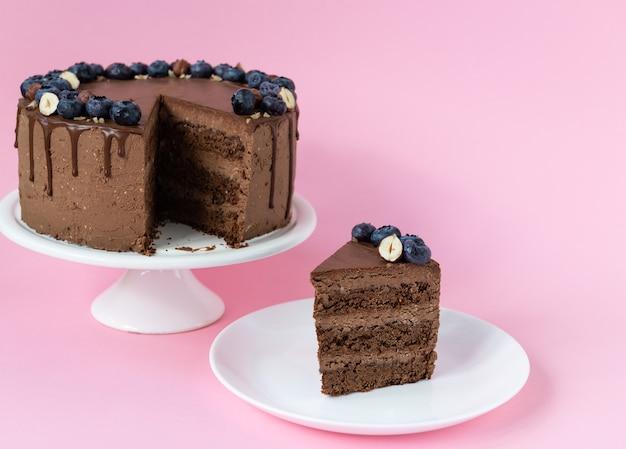핑크 배경에 블루 베리와 견과류와 초콜릿 케이크 한 조각