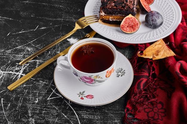 白いプレートにイチジクとお茶とチョコレートケーキのスライス。