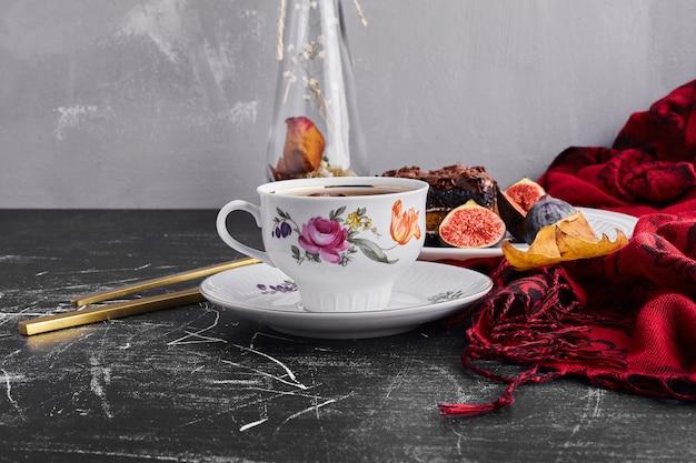 무화과와 차를 곁들인 초콜릿 케이크 한 조각.