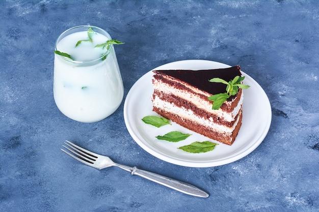 Кусочек шоколадного торта с молоком и мятой.