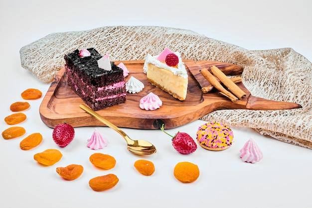 치즈 케이크 한 조각과 초콜릿 카라멜 케이크 한 조각.