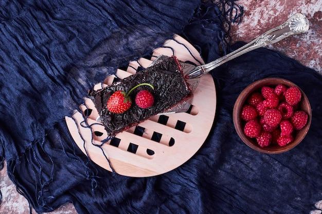 Кусочек шоколадного чизкейка с ягодами.