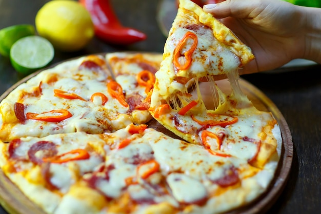 手にモッツァレラチーズのストレッチを添えた新鮮なホットピザのスライス。