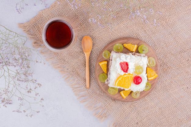 Кусочек фруктового торта со взбитыми сливками и чаем