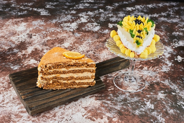 Кусочек медового торта на блюде в деревенском стиле.