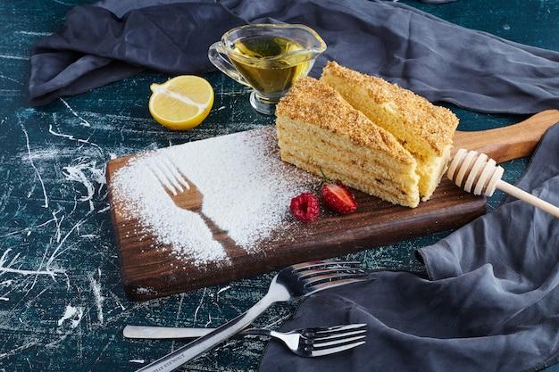 나무 보드에 꿀 케이크 한 조각.