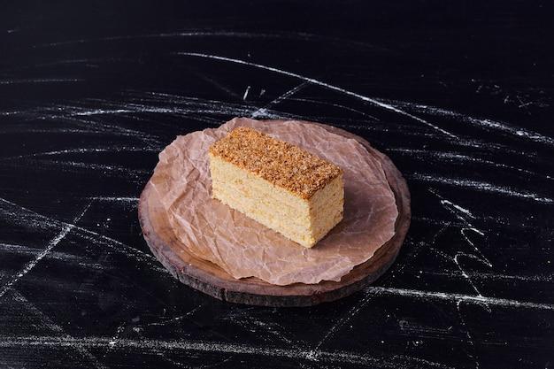 Кусочек медового торта на круглом деревянном блюде.