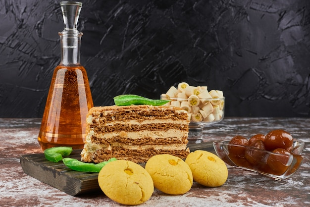 Кусочек медового торта с масляным печеньем и бутылка напитка.