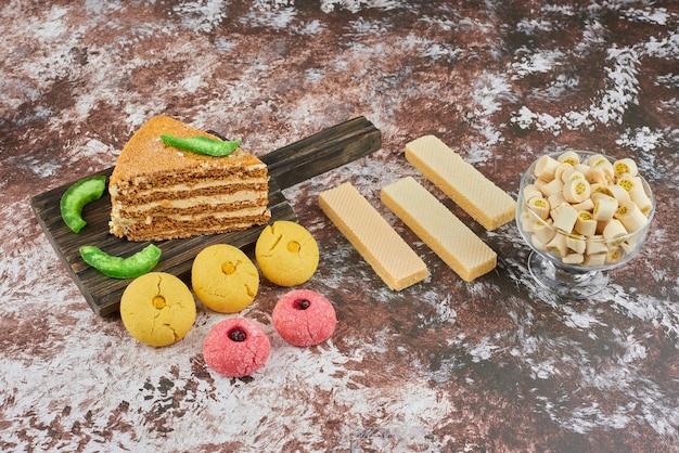 Кусочек медового торта с масляным печеньем и вафлями.