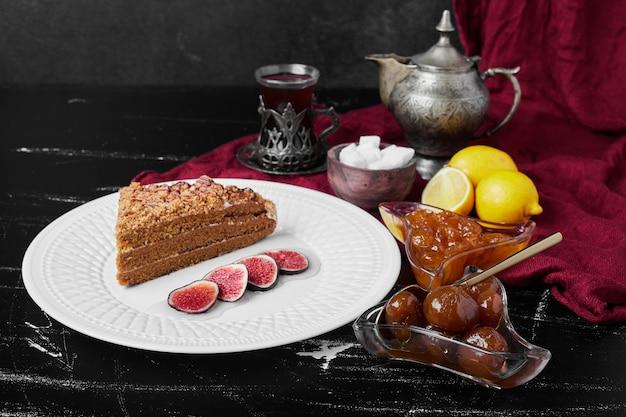 Кусочек медового торта с инжиром и конфитюром.