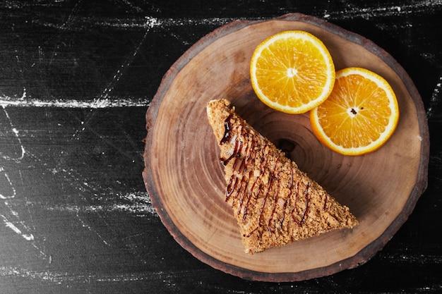 Кусочек медового торта с дольками апельсина.