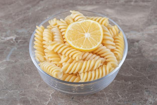 Долька лимона в пасте фузилли на миске на мраморной поверхности.