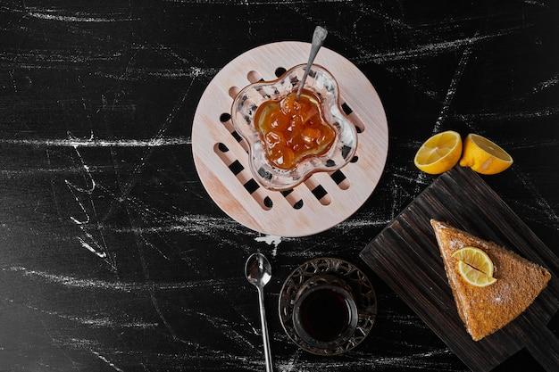 Кусочек медовского торта на черном камне подается с конфитюром и чаем.