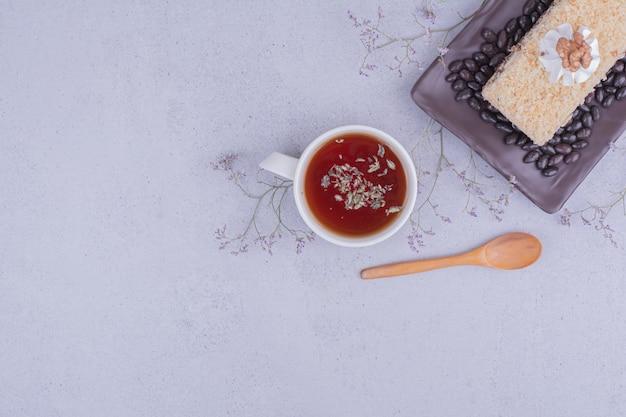 お茶と黒の大皿にチョコレート豆とメドビックケーキのスライス 無料写真