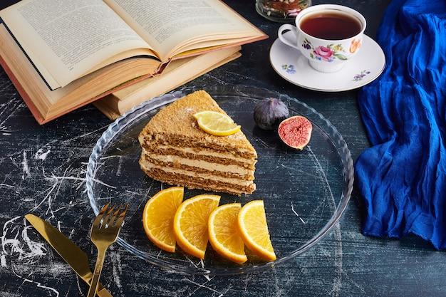 柑橘系の果物とお茶とメドビックケーキのスライス。