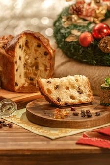 クリスマスの飾りと木製のまな板上のパネットーネと砂糖漬けのフルーツキューブのスライス