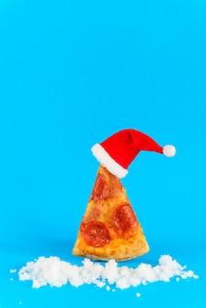 Кусочек пиццы пепперони в виде елки со шляпой санты и снегом на синем фоне.