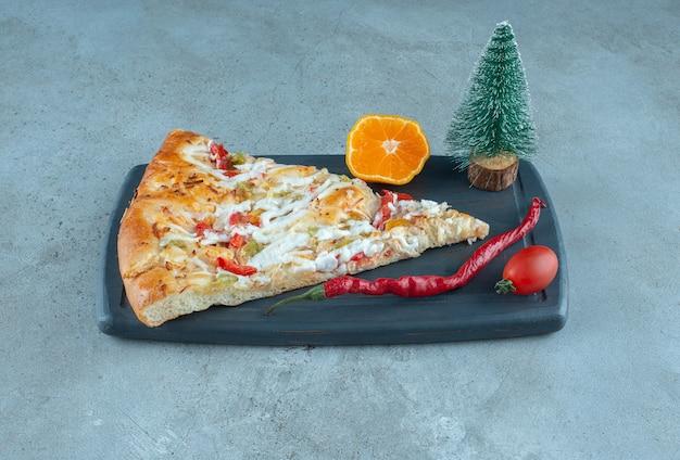 Кусочек пиццы на доске с фигуркой дерева на мраморной поверхности