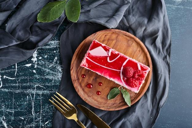 Кусочек красного чизкейка на деревянном блюде, вид сверху.