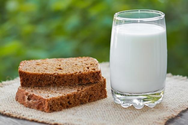 나무 테이블에 호밀 빵과 우유 한 조각
