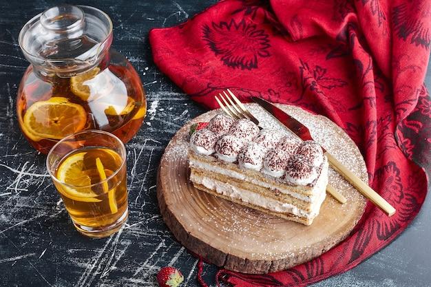 Кусочек торта тирамису со стаканом лимонада.