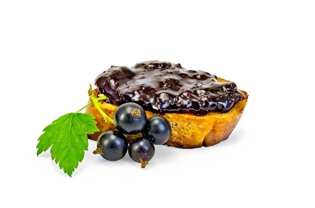 Кусочек тоста с джемом из черной смородины, ветка с ягодами и листьями черной смородины, изолированные на белом фоне