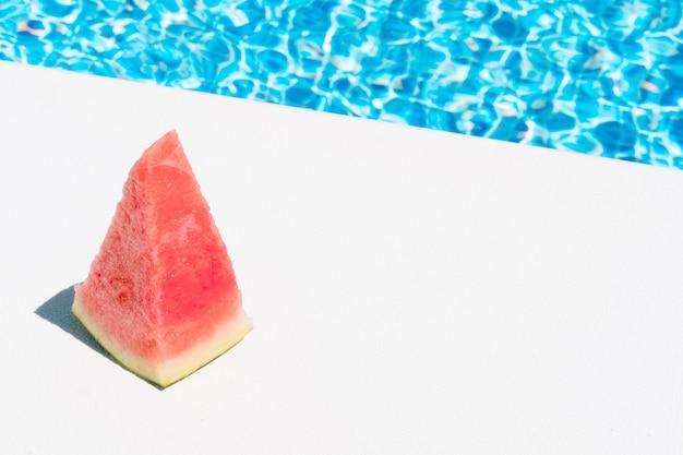 Кусочек арбуза у бассейна концепция летнего отдыха и еды