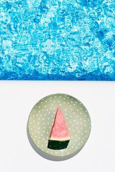 Кусочек арбуза на зеленой тарелке у бассейна концепция летнего отдыха и еды