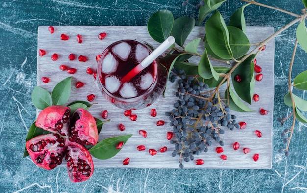 A 파란색 배경에 보드에 석류와 주스의 슬라이스. 고품질 사진