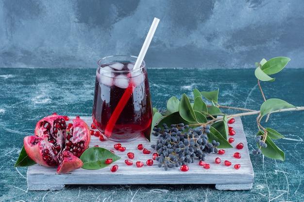 青いテーブルの上のボード上のザクロとジュースのスライス。