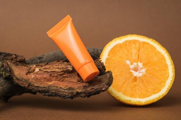 Нарезанный апельсин, апельсиновый тюбик сливок и ветка старого дерева.