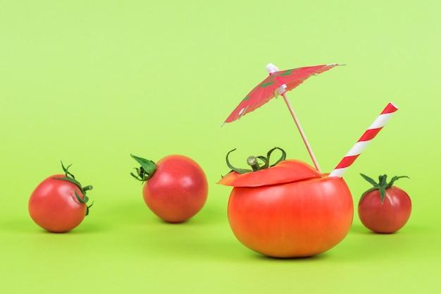 Нарезанный помидор с трубочкой для коктейля и зонтиком на фоне разбросанного помидора.