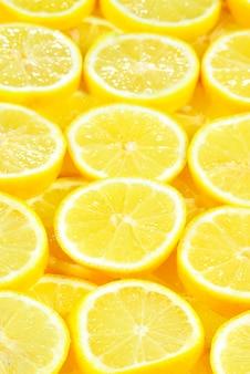 新鮮なジューシーな黄色いレモンのスライス。テクスチャ背景、パターン。