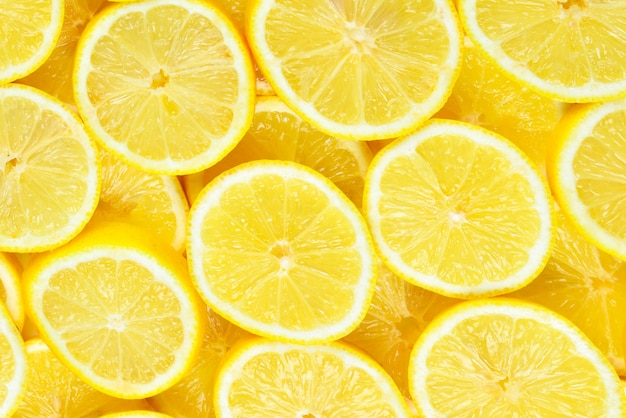 Дольки свежих сочных желтых лимонов. предпосылка текстуры. Premium Фотографии