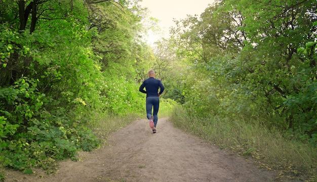 검은 색 스포츠 레깅스, 셔츠 및 스니커즈를 입은 날씬한 운동 조깅하는 사람이 녹색 봄 숲을 달리고 있습니다. 다시보기. 사진은 건강한 생활 방식을 보여줍니다.