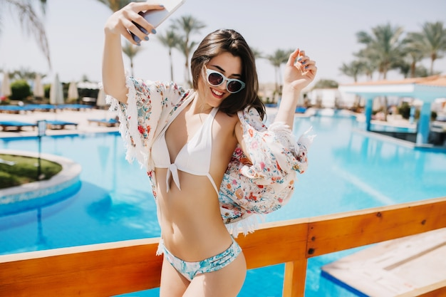 光沢のある茶色の髪とプールのそばでおかしく踊り、南の風景で笑っているスリムな日焼けした女の子。外で楽しんで、休暇で夏の日を楽しんでいるサングラスでゴージャスな若い女性