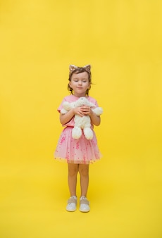 Хитрая девушка в ободке с ушками и пышной юбкой и мягкой игрушкой зайка на желтом с местом для текста