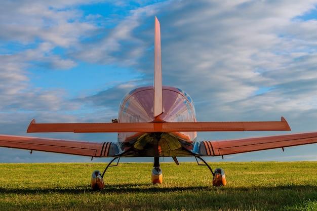 흰 구름과 푸른 하늘을 배경으로 작은 2 인승 비행기. 다시보기. 잔디 필드에 비행기입니다.